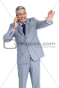 Businessman answering phone and waving