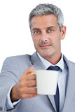Handsome businessman offering cup of coffee