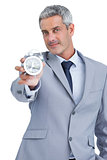 Businessman showing alarm clock