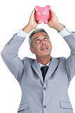 Curious businessman holding piggy bank above his head