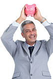 Cheerful businessman holding piggy bank above his head