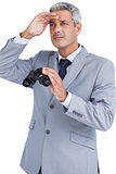 Businessman posing with binoculars and looking away