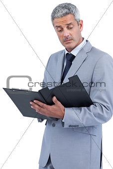 Attentive businessman holding clipboard
