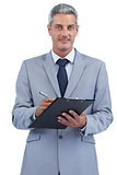 Businessman holding clipboard and taking notes