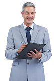 Joyful businessman holding clipboard and taking notes