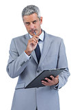 Assiduous businessman holding clipboard and taking notes