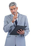 Pensive businessman holding clipboard and taking notes