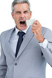 Businessman ripping off duct tape from mouth