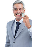 Cheerful man taking away adhesive tape from mouth
