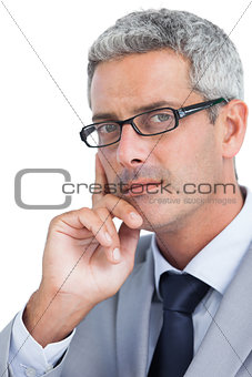 Thoughtful handsome businessman wearing glasses