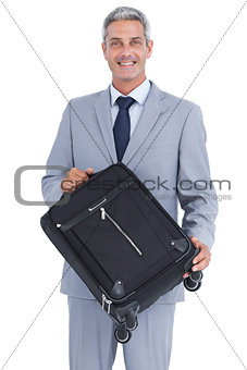 Smiling handsome businessman carrying suitcase