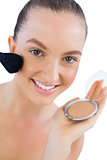 Cheerful young model applying face powder