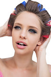 Model with hair curlers touching her hair