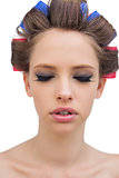 Pretty model with hair curlers closing eyes