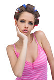 Cute young model posing wearing hair curlers