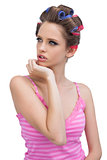 Thoughtful model in hair curlers posing and looking away
