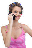 Smiling model with phone wearing hair rollers