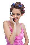 Happy model wearing hair rollers having a call