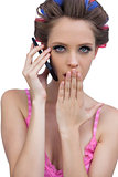 Secretive model wearing hair rollers with phone