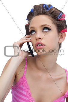 Thoughtful young model wearing hair rollers with phone