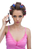Serious woman wearing hair rollers with phone