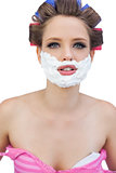 Young model in hair curlers with shaving foam posing