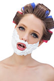 Model in hair curlers with shaving foam in close up