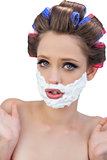 Surprised model in hair curlers posing with shaving foam