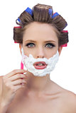 Young model in hair curlers posing with shaving foam and razor