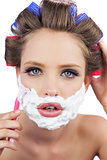 Model in hair curlers posing with shaving foam and razor in close up