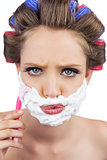 Serious model in hair curlers posing with shaving foam and razor