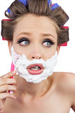 Shocked young model in hair curlers posing with razor