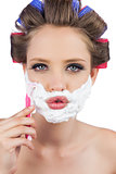 Sexy young model in hair curlers posing with razor