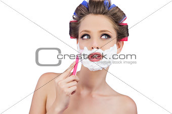 Thoughtful woman in hair curlers posing with razor