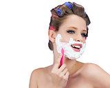 Happy model in hair curlers posing with razor
