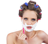 Delightful model in hair curlers posing with razor