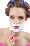 Young model in hair curlers posing with razor