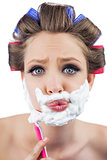 Curious model in hair curlers posing with shaving foam and razor