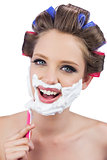 Smiling model in hair curlers posing while shaving