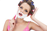 Model in hair curlers shaving her face