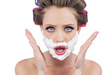 Astonished woman posing with shaving foam on face