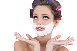 Pensive woman posing with shaving foam on face