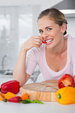 Attractive woman posing while eating vegetables