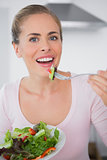 Pretty blonde eating salad