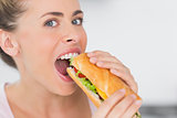 Happy woman eating sandwich and looking at camera