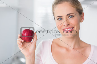 Smiling woman holding apple in right hand
