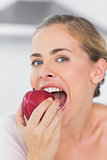 Attractive woman munching red apple