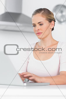 Concentrated woman typing on laptop
