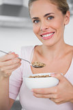 Smiling woman holding bowl of cereal