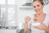 Cheerful woman holding bowl of cereal